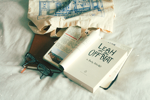 book leah on the offbeat on a bed with bag and notebooks