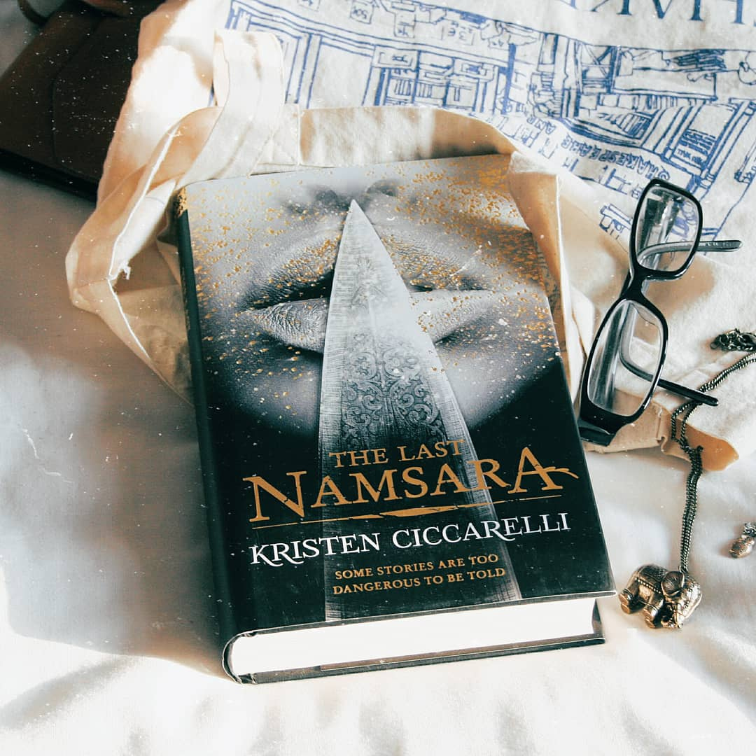 the last namsara book on a bed with glasses and necklace