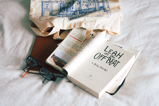 book on bed with tote bag