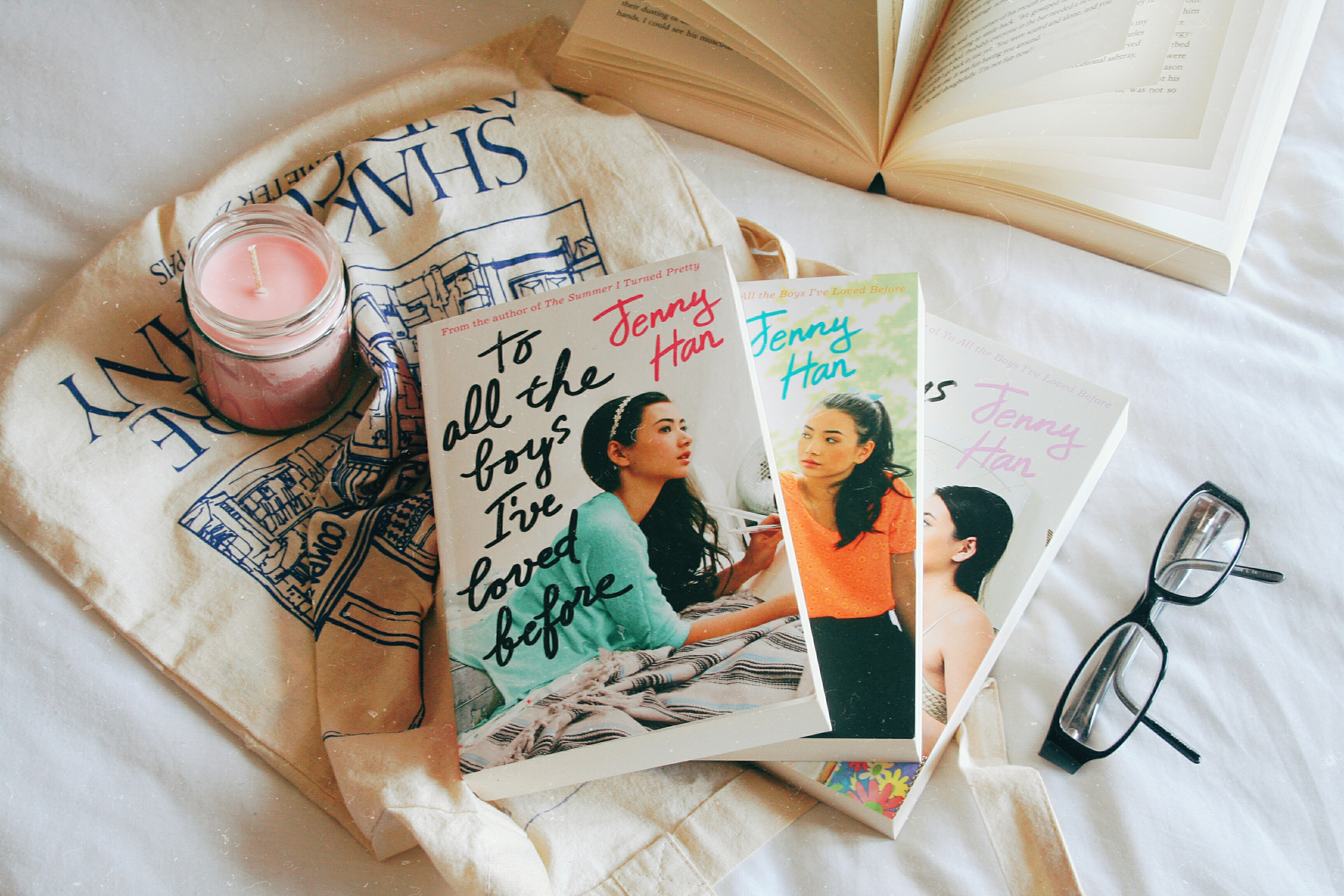 to all the boys i've loved before series on a bed with a candle and tote bag