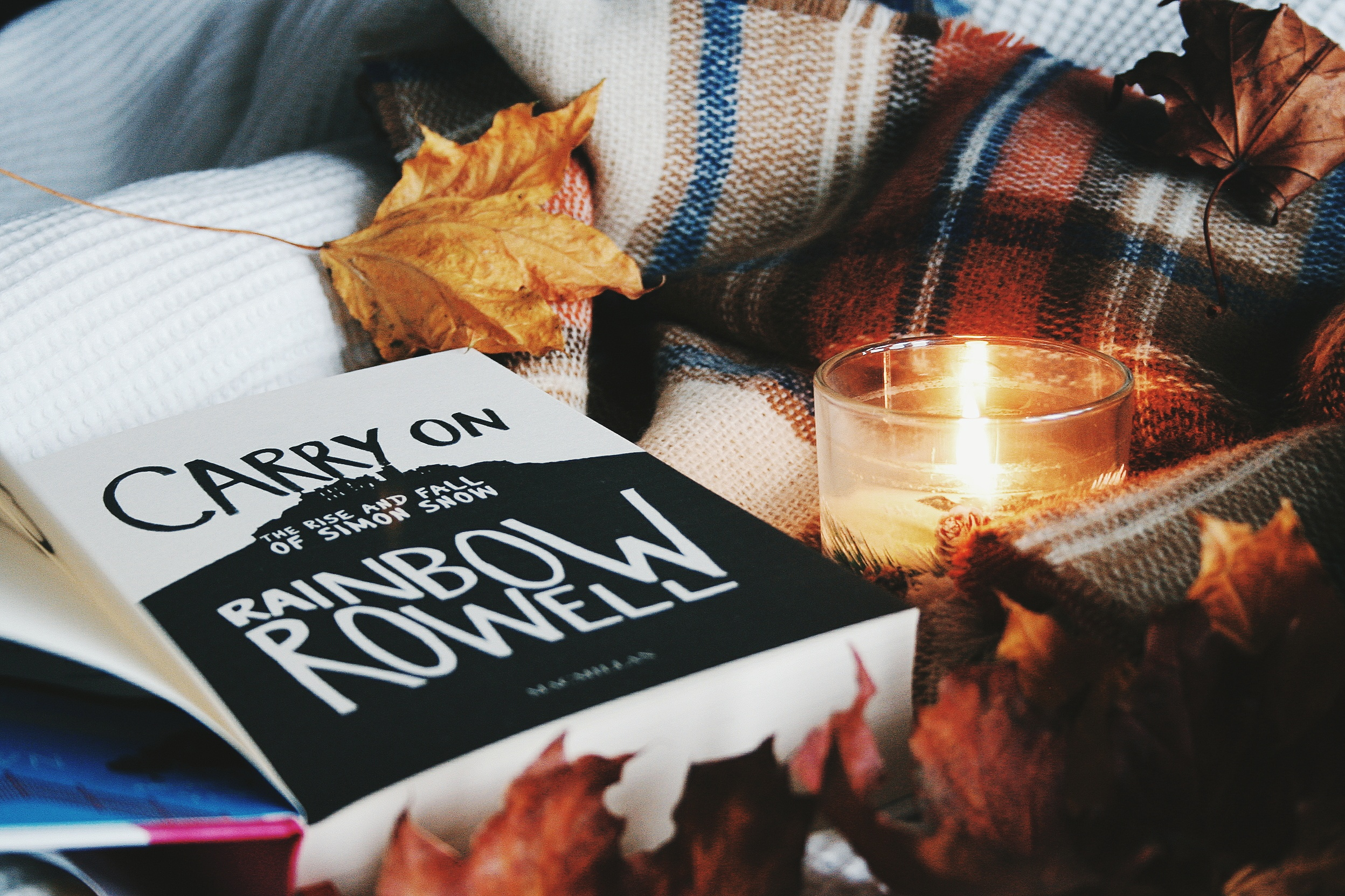 the book carry on by rainbow rowell with a tartan scarf some leaves and a candle