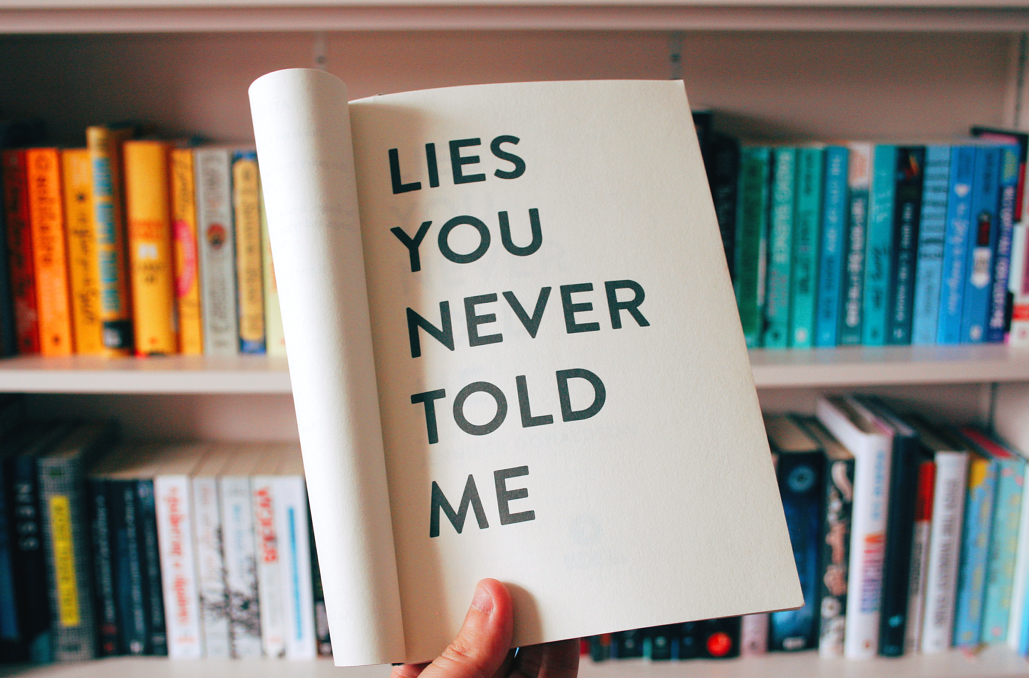 lies you never told me book in front of colourful book case
