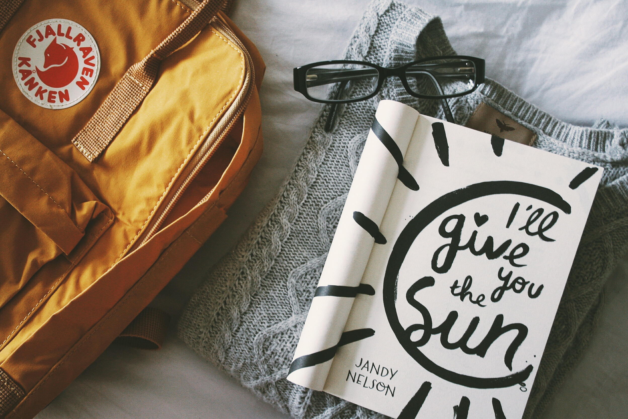 i'll give you the sun by jandy nelson on a bed next to a yellow backpack
