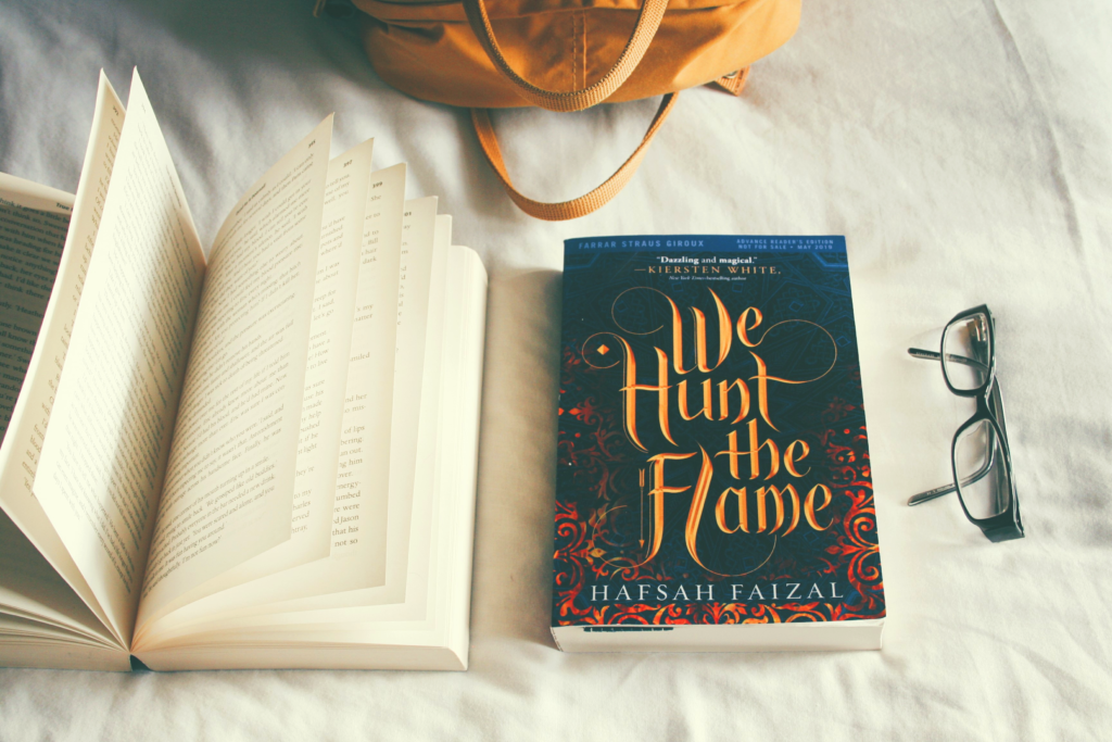 we hunt the flame book on a bed next to open book
