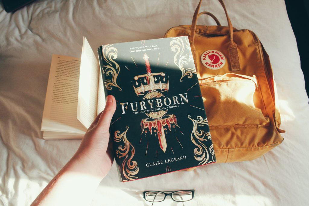 Furyborn hardcover book in front of a backpack