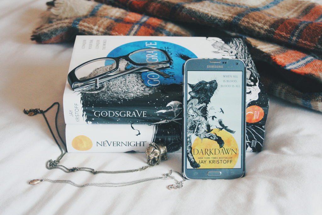 Darkdawn cover on phone along with hardbacks of Nevernight and Godsgrave