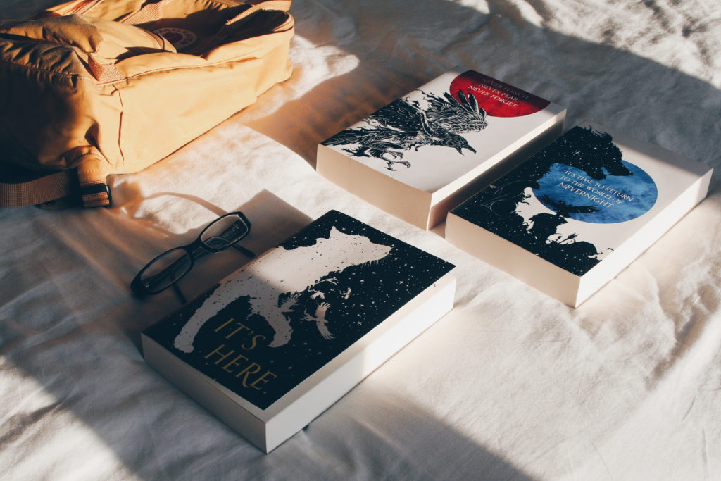 The Nevernight Chronicles including Darkdawn lying on a bed in the sunlight
